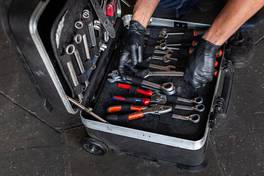 From above unrecognizable male technician picking screwdriver bits from tool box while working in garage