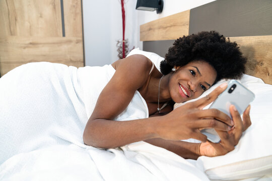 Smiling African American female lying in bed in morning and browsing mobile phone after awakening