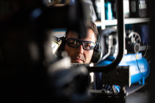 Attentive adult skilled male mechanic in protective goggles and headphones with flashlight in hand examining mechanism during repair service in workshop