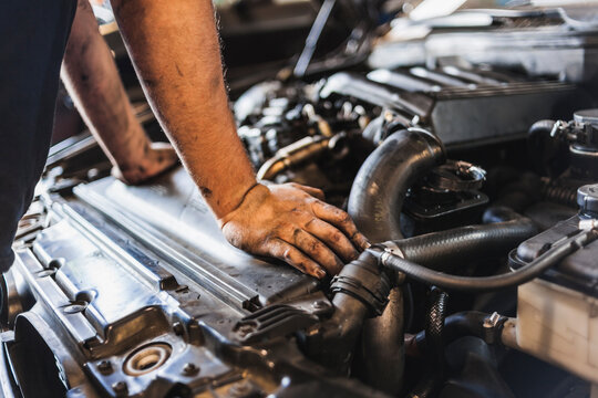 Cropped unrecognizable male mechanic with greasy hands checking motor of vehicle during work in garage