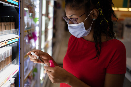 Afro latina young woman wearing a face mask shopping make up products
