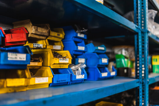 Colorful crates with nails and screws stacked on metal shelf inside professional garage