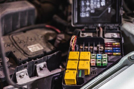 High angle of open relay and fuse box installed inside vehicle near battery during repair works in garage
