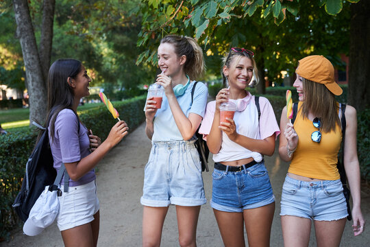 Group of cheerful diverse hipster girlfriends enjoying takeaway cold beverages and fruit ice cream in summer park
