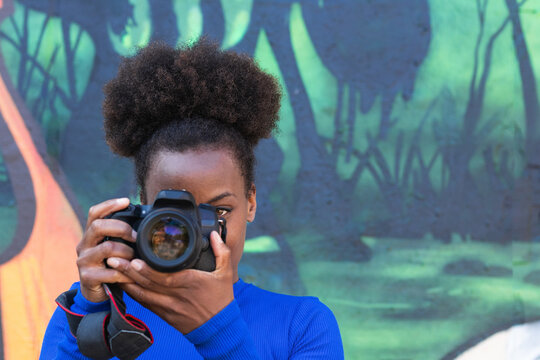 Focused African American professional female photographer with photo camera taking pictures while standing on street against wall with graffiti