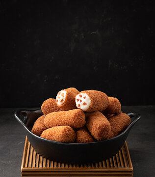 Croquettes served in a bowl on dark background
