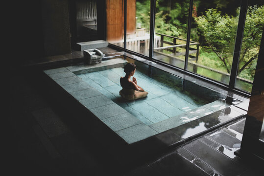 Young caucasian woman kneeling inside a thermal waters bath and meditating with hands in prayer at a traditional Japanese onsen