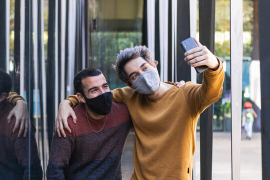 Delighted male friends wearing protective masks standing in street and taking selfie on smartphone during coronavirus