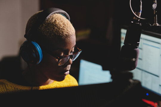 Side view of african American female radio host working in dark broadcast studio and speaking in microphone