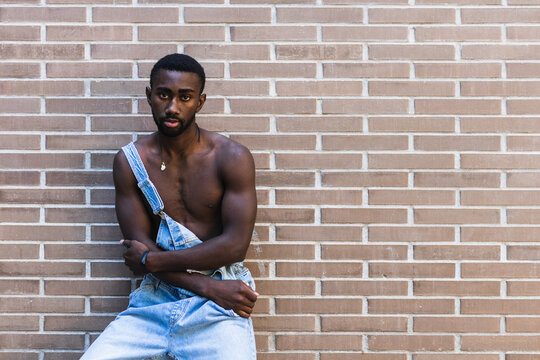 African American male with muscular naked torso standing in denim overalls in city on background of brick wall and looking at camera
