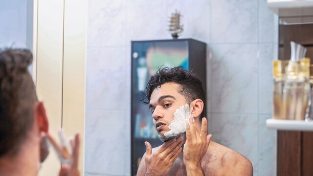 Young dark haired male with foam on face and neck looking at mirror and shaving beard with manual razor in bathroom