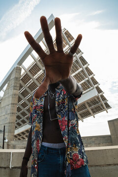 Low angle of anonymous young African American male in unbuttoned colorful shirt outstretching hand towards camera and doing protest gesture while standing against modern urban building