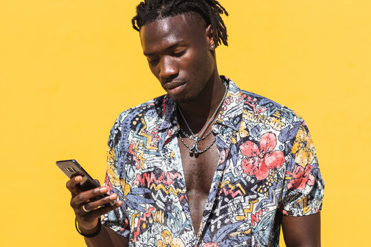 Confident young hipster African American male with dreadlocks wearing trendy summer shirt with floral print and jeans using mobile phone against yellow background