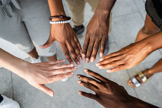 High angle of crop unrecognizable multiracial company of friends stacking hands together on street on sunny day
