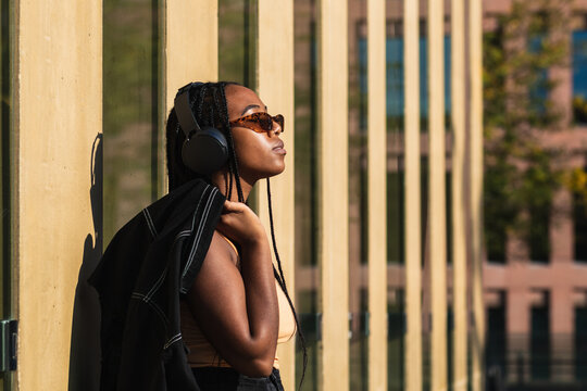 Side view of young black woman with stylish jacket leaning on wall of contemporary building and listening to music in headphones on city street
