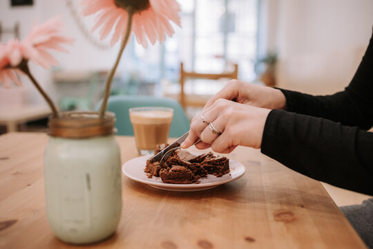 Side view of crop anonymous female eating delicious chocolate cake while sitting at table with glass of coffee in cozy confectionery cafe
