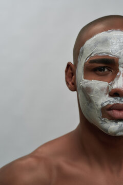 Half face portrait of shirtless young african american man looking at camera using facial clay mask, posing isolated over gray background
