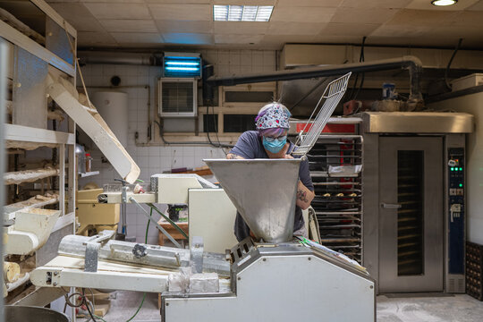 Female baker in protective mask cleaning metal baking machine from dough while working in bakehouse