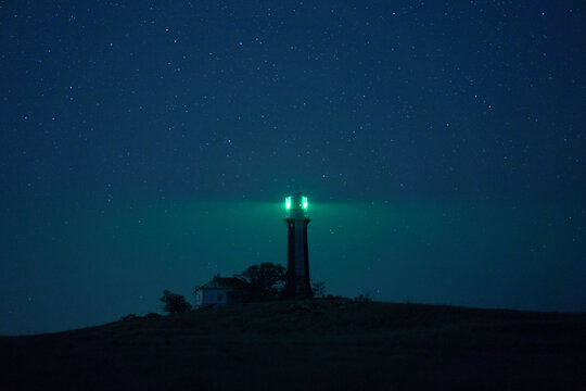 Beacon tower located on hill and illuminating darkness with green light on background of starry night sky
