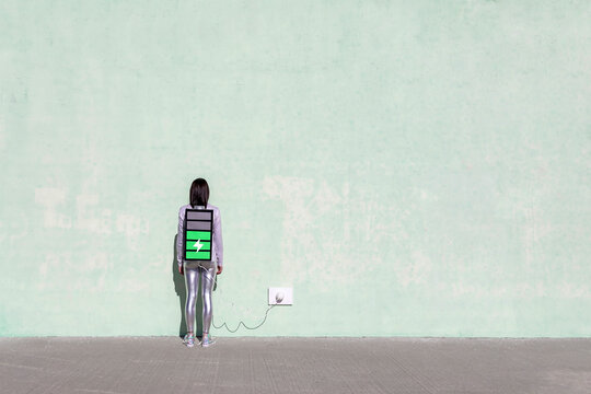 Back view of unrecognizable female with long dark hair in stylish outfit standing on street near wall with battery shaped backpack connected to charger