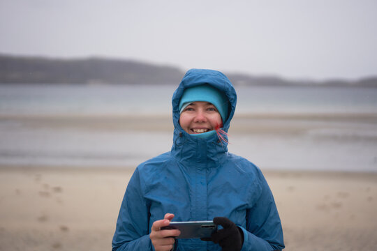 Delighted female explorer in warm waterproof jacket standing with cellphone at seaside on windy day and looking at camera