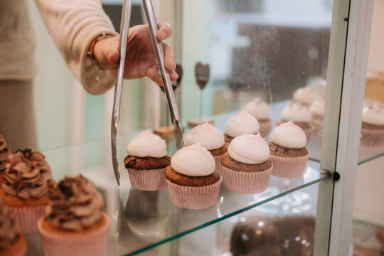 Crop anonymous female seller with tongs taking delicious cupcake with white cream from glass display while working in confectionery shop