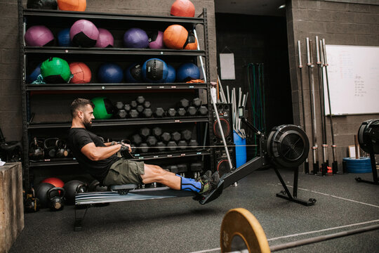 Side view of athletic male with strong body doing exercises on rowing machine in modern sports club