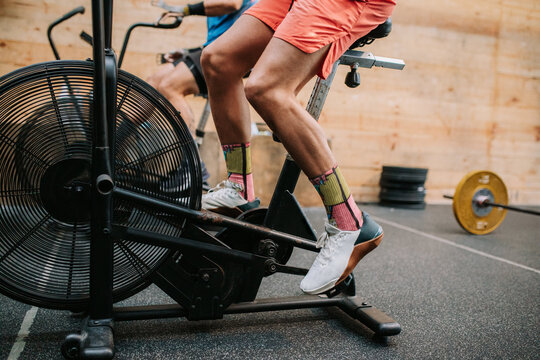 Cropped unrecognizable active male athletes doing exercises on air cycling machines during intense workout in gym