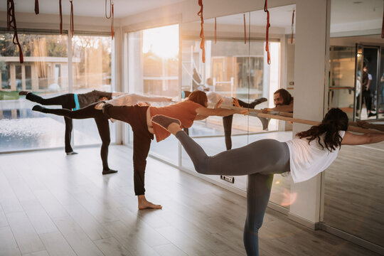 Side view of company of people in activewear standing near barre and doing yoga in Virabhadrasana while balancing on leg