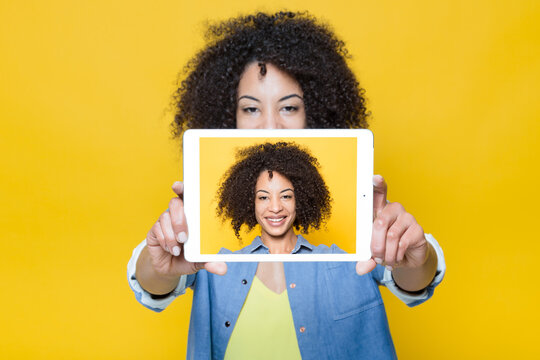 Happy young African American female with curly hair taking selfie with digital tablet on bright yellow background