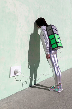 Side view of unrecognizable exhausted female in futuristic outfit leaning head on wall while standing on street and recharging energy