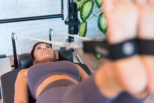 Fit woman doing legs exercise with resistance ropes on Pilates reformer in gym