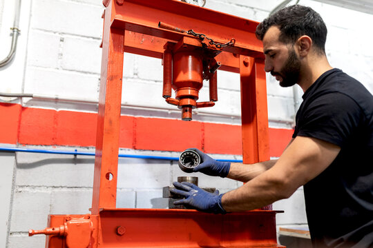 Side view low angle of male technician using hydraulic press for car bearing while working in service
