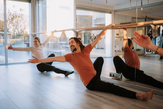 Flexible people in activewear sitting in Skandasana near barre and stretching body while doing yoga together in studio
