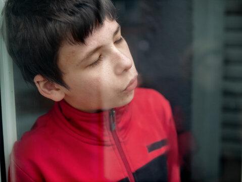 Teen sulks over house arrest looking through a window
