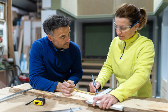 Concentrated adult male and female masters in uniforms measuring wooden board standing at table with laptop and instruments in modern workshop