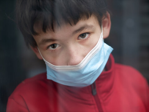 Teenage boy with medical mask at home behind a window