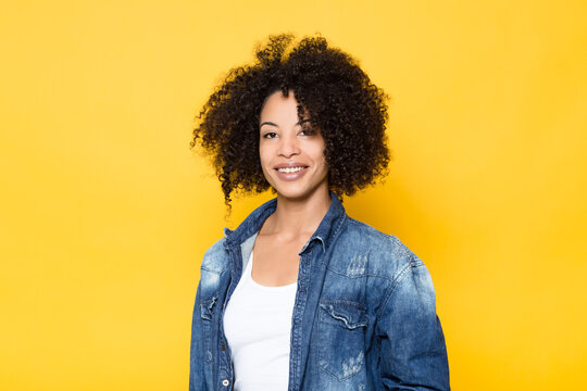 Positive young curly haired African American female in trendy denim outfit smiling and looking at camera while standing against yellow background