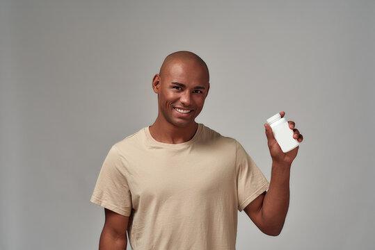 Display of a pill bottle in a joyful man arm