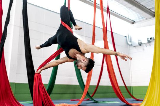 Bearded adult dancer in black leotard hanging upside down on aerial silk during rehearsal in studio