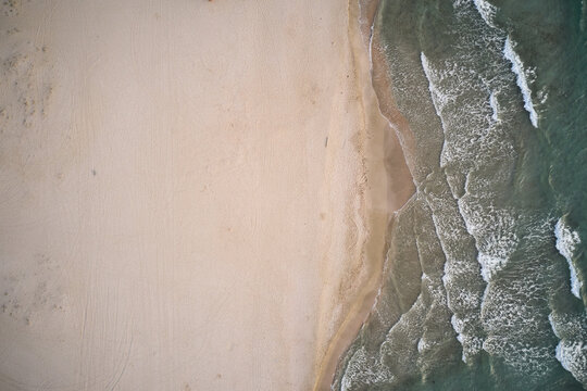Aerial top view of turquoise water with seaweed and foamy waves rolling on empty sandy beach