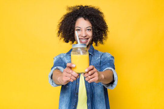 Cheerful young curly haired African American female in casual outfit looking at camera friendly and demonstrating glass jar with healthy fresh orange juice while standing against yellow background