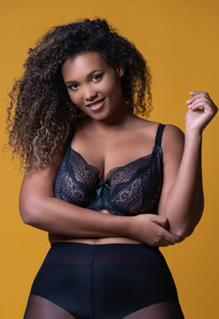 Plus size cheerful African American female model with long curly hair wearing elegant lace underwear looking at camera against yellow background