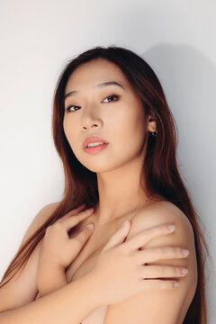 Portrait of naked young Chinese woman looking at camera over white background