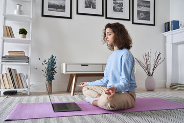 Fototapeta Healthy young woman meditating at home watching online tv yoga class e tutorial on laptop computer doing virtual pilates exercises, breathing, relaxing body and mind, mental health care concept. obraz