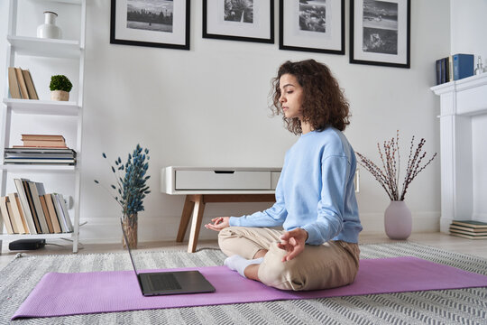 Healthy young woman meditating at home watching online tv yoga class e tutorial on laptop computer doing virtual pilates exercises, breathing, relaxing body and mind, mental health care concept.