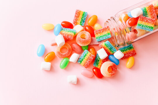 Mixed colorful candies scattered from glass bottle on pink background. Close up