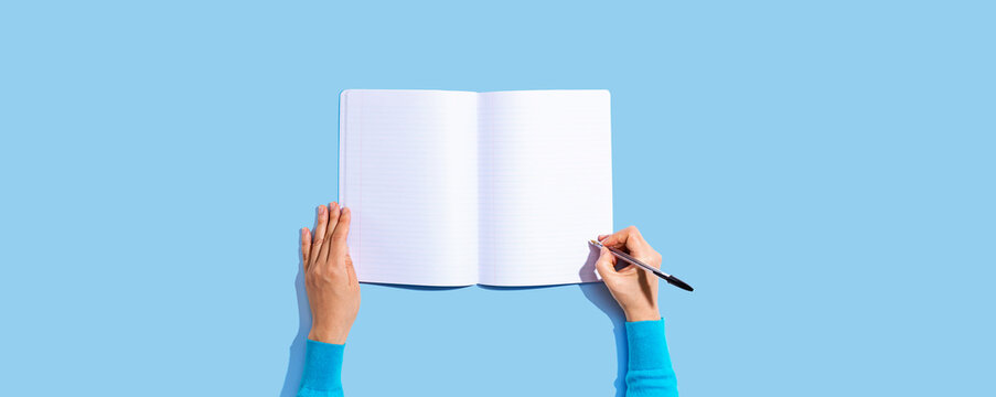 Person writing in a notebook from above