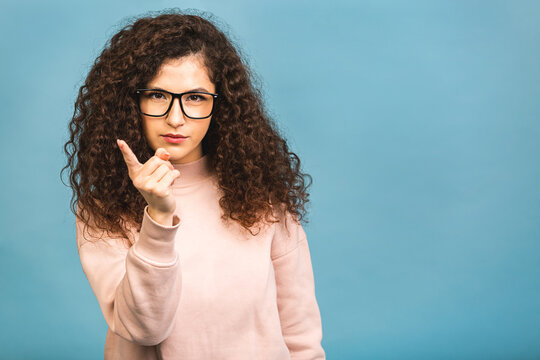 Attention, listen to me! Close up portrait of young curly woman wagging her finger isolated over blue background. Negative human emotions facial expression.