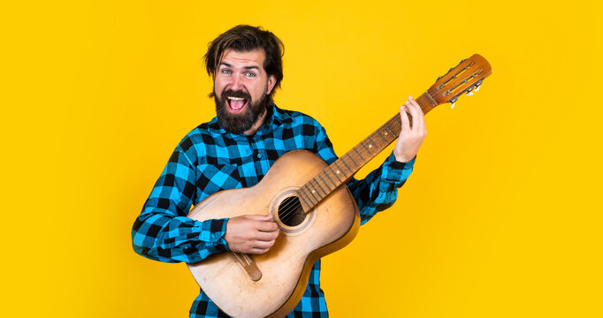 mature guitarist playing the guitar on yellow background, vocal